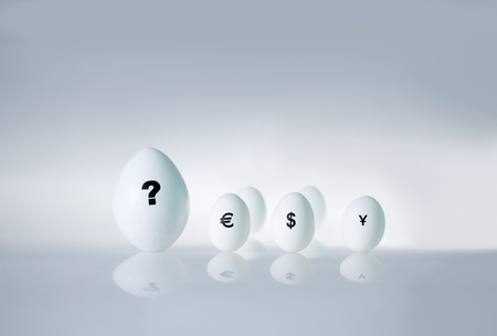 Close-up of big egg with question mark on it and several small eggs with currency signs photo