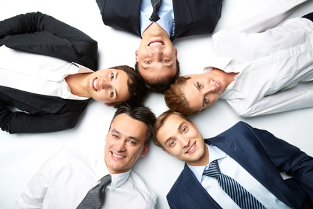 Five business people lying on the floor, looking at camera and smiling photo