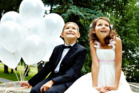 Portrait of children bride and groom with balloons sitting in park  photo