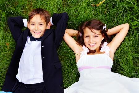 Portrait de la mariée et le marié enfants souriants couché sur l'herbe verte et regardant la caméra