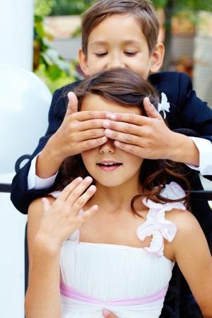 Portrait of boy groom shutting eyes of his bride photo