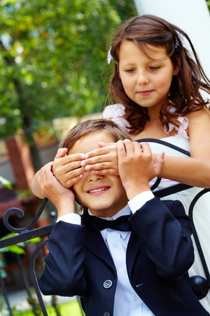 Portrait of cute girl bride shutting eyes of her groom by hands photo