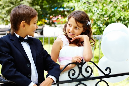 Portrait of boy groom and his cute bride chatting in park photo