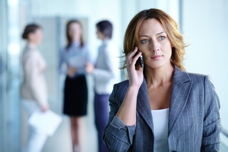 calling communication: Image of pretty businesswoman calling on the phone in working environment