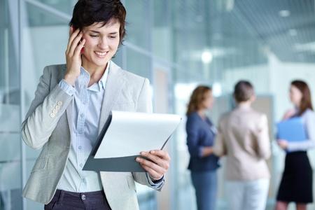 agente comercial: Imagen de la vocación femenina ocupada en el documento de teléfono y la lectura en el entorno de trabajo