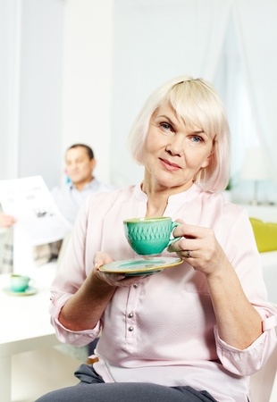 Portrait of mature woman with cup looking at camera on background of her husband Stock Photo - 12325055