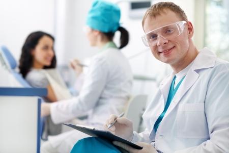 Un dentista apuesto sonriendo a la c�mara con una enfermera y un paciente en el fondo photo