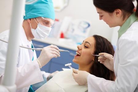 hygienist: Pretty patient undergoing a dental check Stock Photo