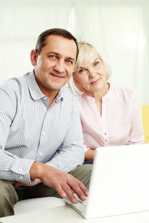 personas comunicandose: Retrato de hombre maduro y su esposa con el ordenador portátil mirando a la cámara