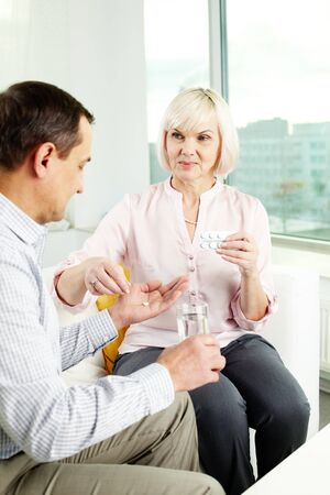 Portrait of mature woman giving tablets to her husband at home Stock Photo - 12325059