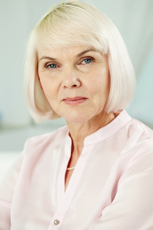 congenial: Portrait of mature blond female looking at camera