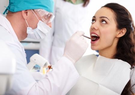 work checkup: Dentist examining his patient's teeth Stock Photo