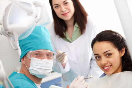 dental mirror: Dentist, his assistant and a patient looking at camera and smiling