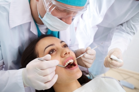 oral surgery: Dentist and his assistant carrying out a thorough examination