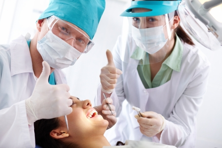Successful dentist and his assistant expressing positivity about their work photo