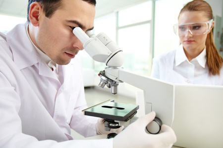Serious clinicians studying chemical elements in laboratory photo
