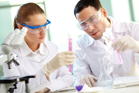bioteknik: Porträtt av två kemister håller rör med rosa vätska