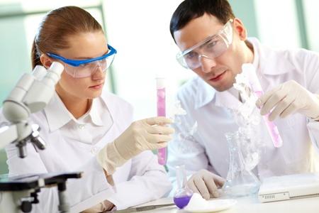 biotecnologia: Retrato de dos qu�micos celebraci�n de tubos con l�quido de color rosa