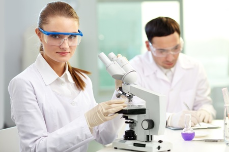 Pretty clinician with microscope looking at camera in laboratory photo