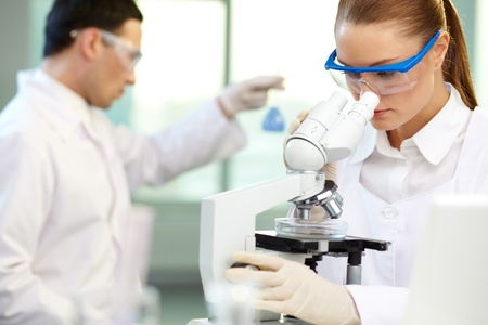 clinician: Serious clinician studying chemical element in working environment