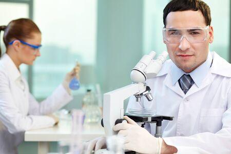 biotecnologia: Retrato de médico joven mirando a la cámara en el entorno de trabajo Foto de archivo