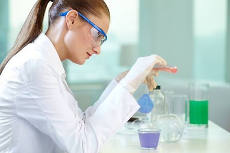 Image of research worker mixing substances at the lab photo