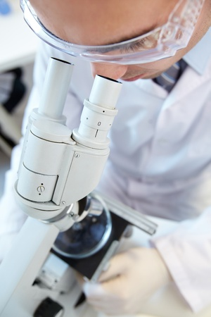Male scientist in protective eyeglasses looking through the microscope Stock Photo - 12319565