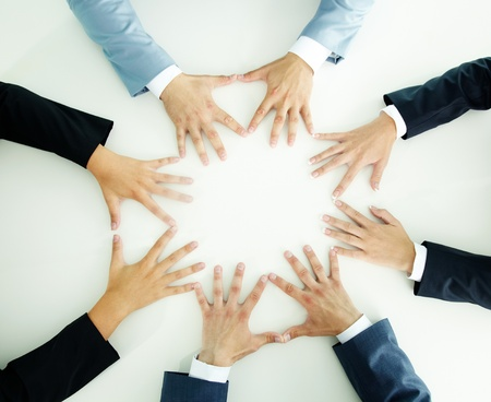 coalition: Top view of businesspeople holding hands together on a plain white surface Stock Photo