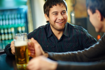 Happy man with glass of beer looking at his friend in pub photo