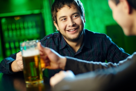 Two guys hanging out in bar with mugs of beer photo