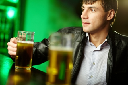 alehouse: Young man sitting at bar counter with a pint of light beer