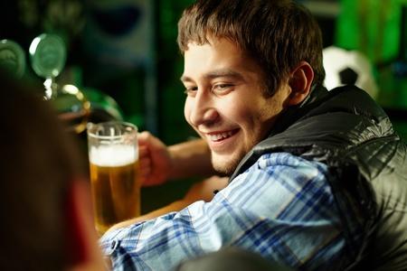 amigas conversando: Alegres amigos varones que pasan tiempo juntos en el bar y bebiendo cerveza Foto de archivo