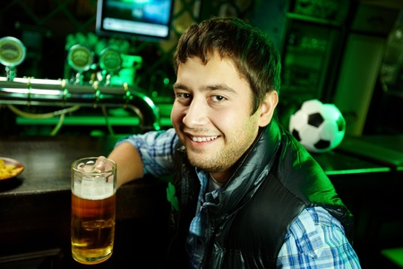 alehouse: Portrait of a positive young man holding a mug of beer and looking at camera