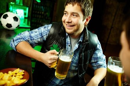 Happy man with glass of beer looking aside in pub photo