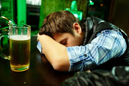 Young man sleeping in pub with glass of beer near by photo
