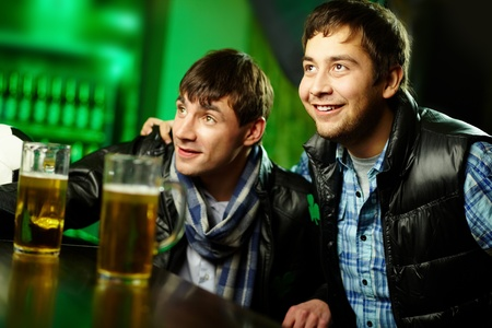 Two friends spending time at sport bar enthusiastic about the game photo