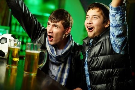sports bar: Two guys watching sports at bar and rejoicing