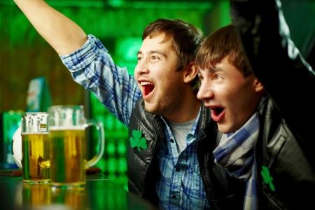 Gelukkig mannen schreeuwen tijdens het kijken naar voetbalwedstrijd uitgezonden in pub
