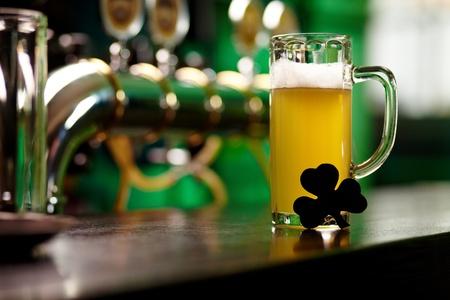 Afbeelding van glas bier met shamrock blad op cafe tafel