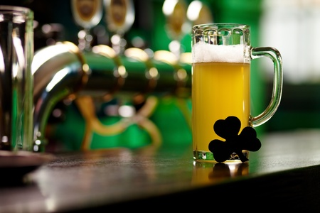 Image of glass of beer with shamrock leaf on pub table Stock Photo