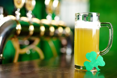 alehouse: A glass of beer on a bar counter with a leaf of shamrock