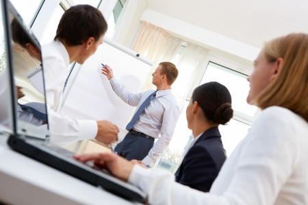 dirección empresarial: Hombre de negocios que presenta el proyecto al equipo de compañeros de trabajo