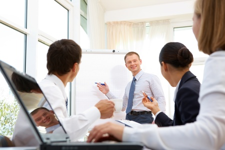 Smiling businessman explaining business ideas to his partners photo