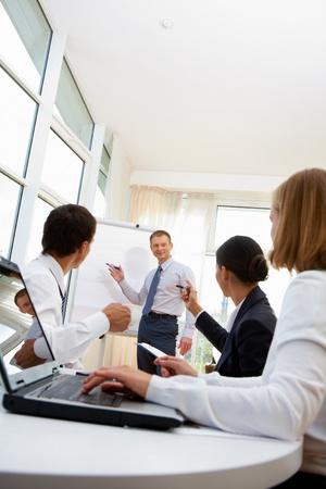 gerente: Sonriente hombre de negocios discutir proyecto de empresa con sus empleados