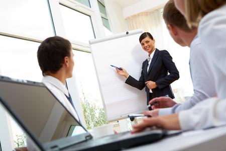 dirección empresarial: Sonriendo empresaria mostrando sus colegas un nuevo proyecto