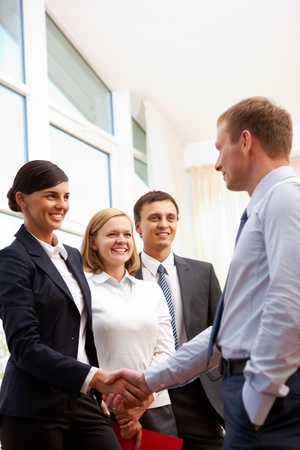 joining hands: Image of business partners handshaking while making deal Stock Photo