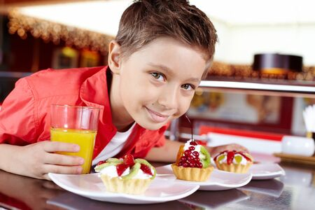 Close-up of a smiling boy with pastry and a glass of orange juice photo