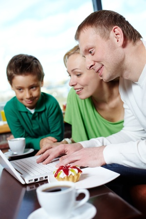 Family of three spending time at a cafe surfing internet Stock Photo - 12326508
