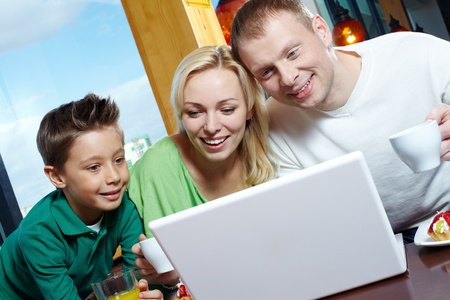 Happy family of three using a laptop while having lunch Stock Photo - 12326593