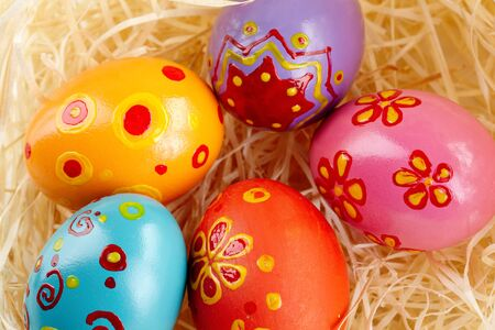 creative egg painting: Close-up of painted Easter eggs in straw Stock Photo